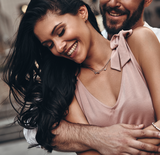 man hugging woman from behind smiling
